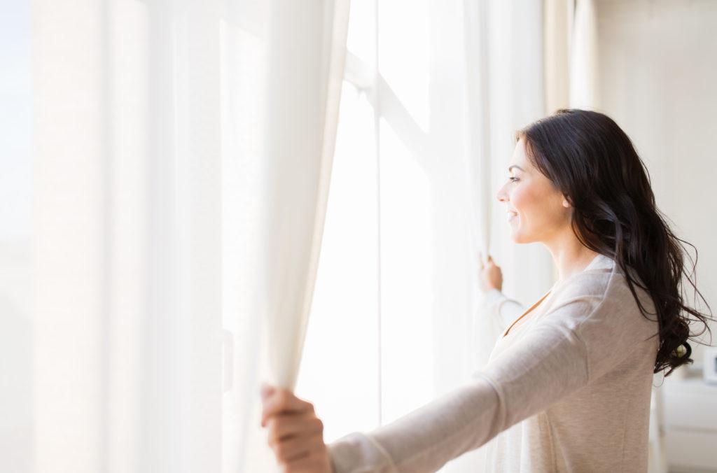 Femme qui aère son logement. Ouverture des rideaux et de la fenêtres