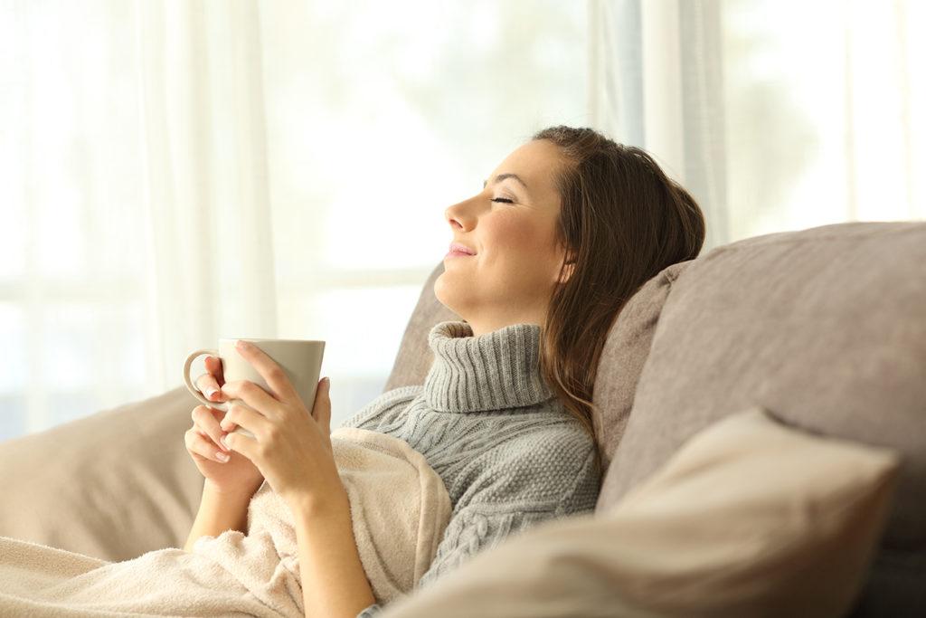 Femme détendue à la maison grâce à la rénovation de ses fenêtres